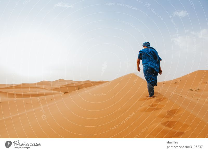 Ein arabischer Mann in blauer Kleidung läuft auf einer Wüstendüne. Lifestyle Ferien & Urlaub & Reisen Tourismus Ausflug Abenteuer Expedition Mensch Erwachsene 1