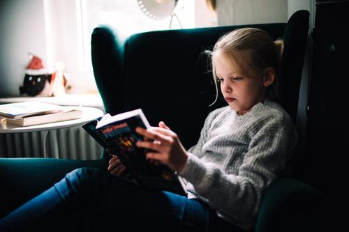 Kind am lesen Häusliches Leben Wohnung feminin Mädchen Kindheit 1 Mensch 8-13 Jahre Jugendkultur Medien Printmedien Zeitung Zeitschrift Buch Comic Erholung