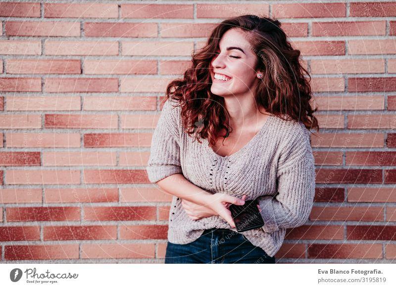 junge Frau, die in der Stadt im Freien mobil telefoniert Jugendliche benutzend Handy Technik & Technologie Internet Großstadt Wand Backstein Lächeln Glück schön