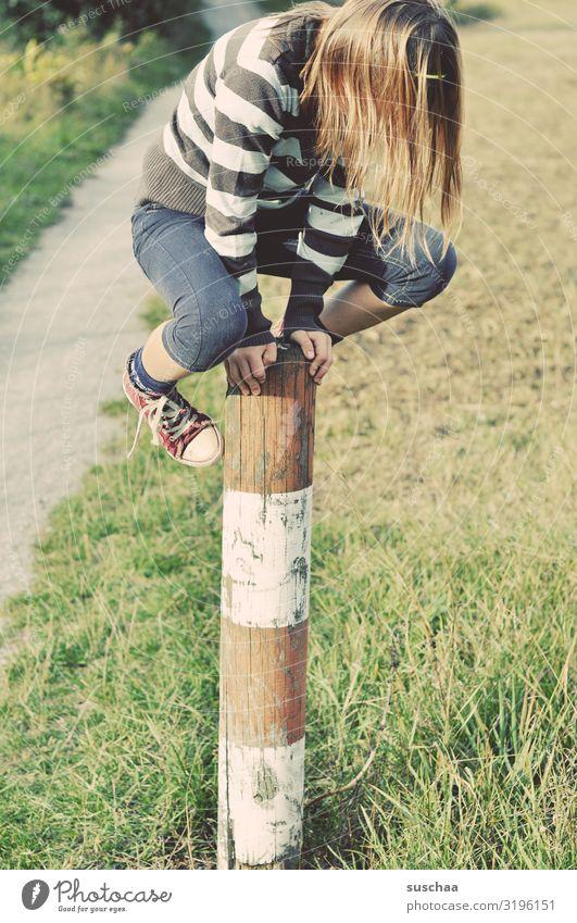 kletterin Kind Mädchen jungennhaft Klettern Spielen gewagt Pfosten Holzpfahl Zaunpfahl festhalten Außenaufnahme Fußweg Natur toben Kindheit Geschicklichkeit
