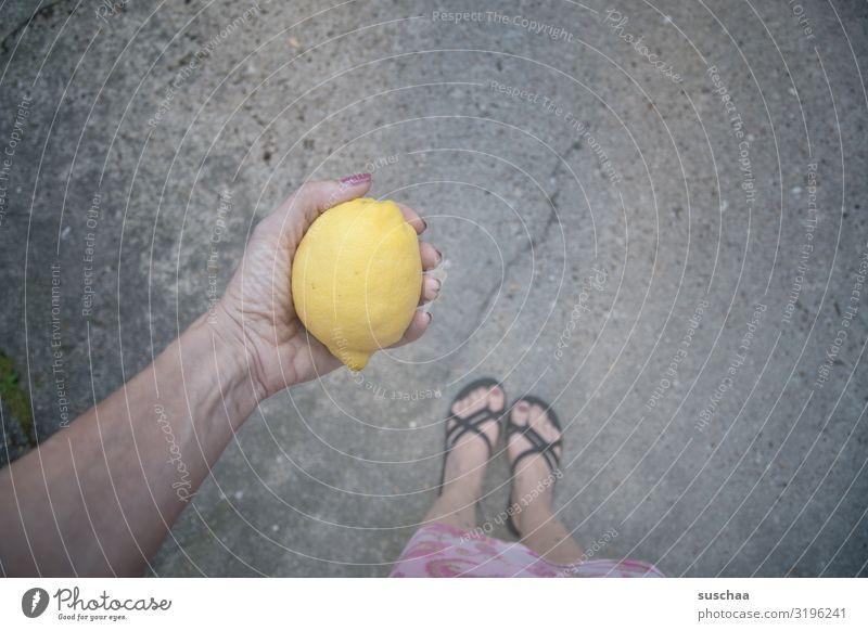 Vitamin C Frau Gesunde Ernährung Sommer Hand Gesundheit Straße gelb Frucht stehen Asphalt zeigen Zitrone geben sauer Flipflops Zitrusfrüchte
