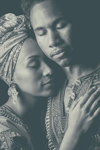 Frau zieht Hand an Gesicht des Mannes. umarmend angestammt Ohrringe Freiheit Fürsorge urwüchsig Schmuckanhänger Accessoire Nationalitäten u. Ethnien romantisch