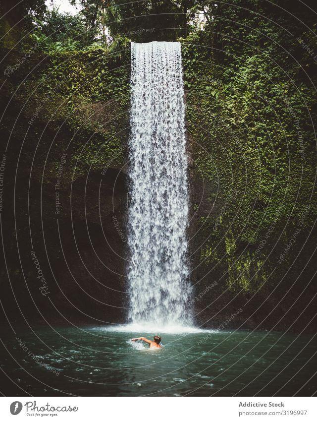 Mann schwimmt in türkisfarbener Naturbucht Im Wasser treiben tropisch Wasserfall See Bali Bucht anschaulich frisch Tourismus harmonisch Ferien & Urlaub & Reisen
