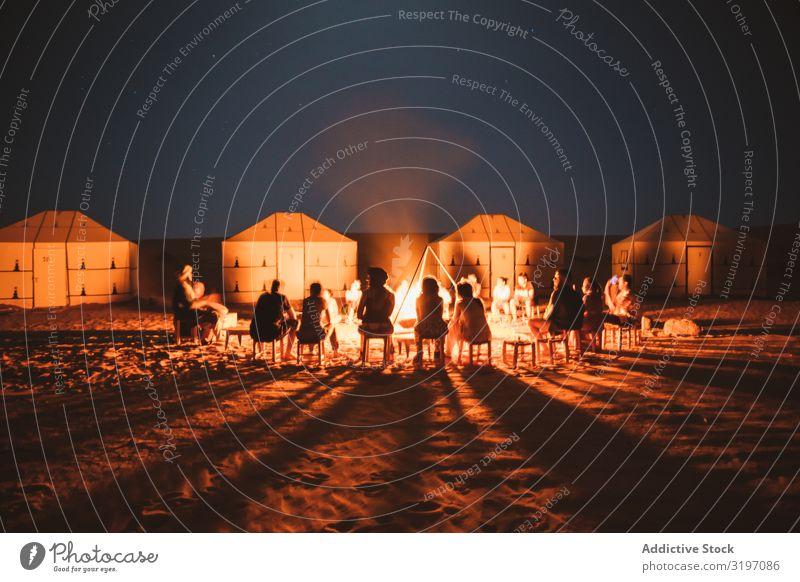 Menschen versammeln sich um das brennende Feuer in der Wüste. Tourist Freudenfeuer Nacht Zelt Marokko Camping Ferien & Urlaub & Reisen Menschengruppe hell