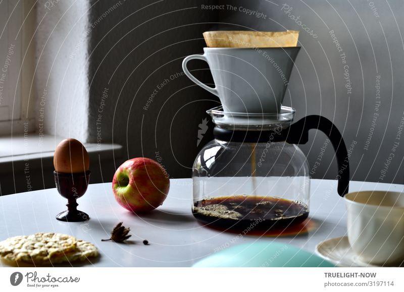 Gläserne Kaffeekanne, weisser Porzellanfilter, hellbraunes Filterpapier und dunkelbrauner durchlaufender, Bläschen bildender Kaffee, Apfel, Ei in hölzernem Eierbecher, weisse Tasse, Maiswaffeln, weisser Tisch vor grauer Wand im Morgenlicht.