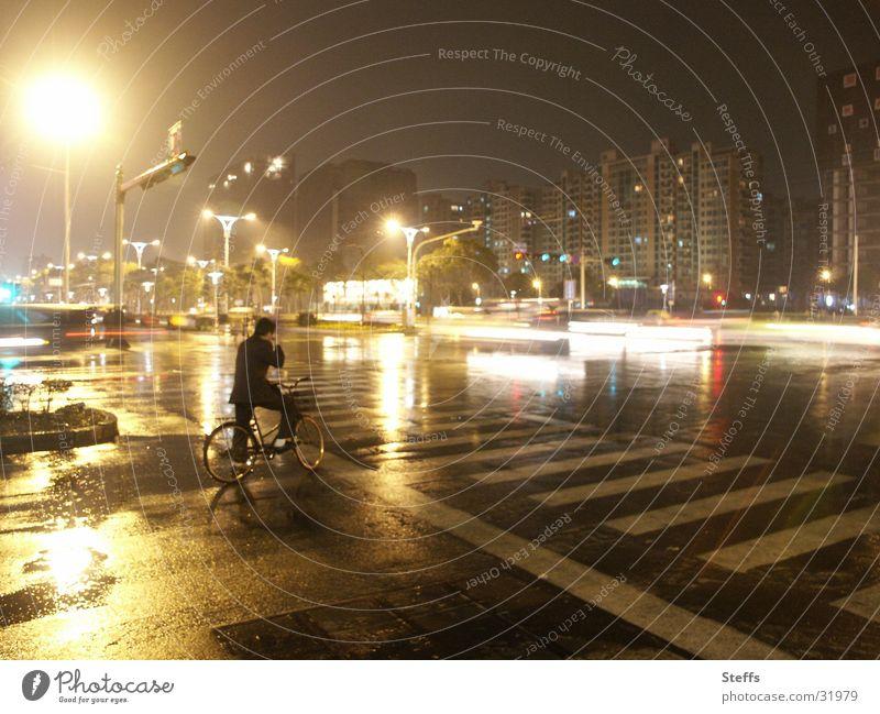 chinesische Strasse im Regen Mann Einsamkeit gelb Straße dunkel grau Stimmung Fahrrad Verkehr China Straßenbeleuchtung Straßenkreuzung Chinesisch Übergang
