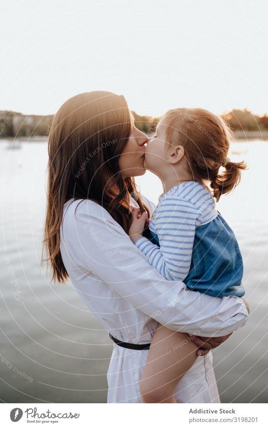 Mutter und Tochter am Wasser stehend Küste Park umarmend tragen Abend Lifestyle Freizeit & Hobby Frau Mädchen Kind Liebe Angebot Fluss Teich See Eltern