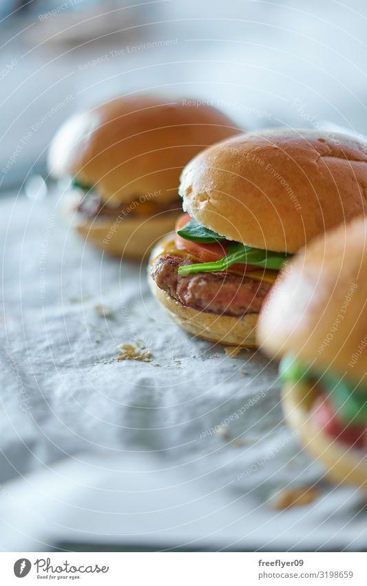 Hausgemachte Hamburger auf Backpapier Fleisch Käse Gemüse Brot Brötchen Ernährung Mittagessen Fastfood Gastronomie Papier Zettel frisch lecker natürlich