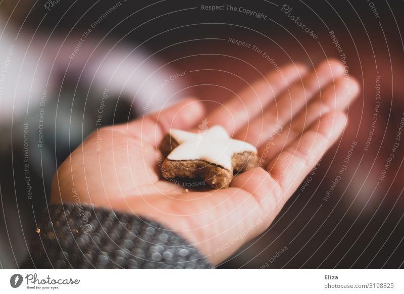 Ein Mensch, der einen Zimtstern in der Hand hält; Weihnachten, Advent, Weihnachtsbäckerei Weihnachten & Advent feminin 1 Plätzchen Freundschaft Keks backen