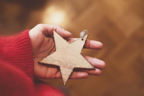 Eine Person die einen Stern aus Holz in der Hand hält; Weihnachten, Advent Weihnachten & Advent Baumschmuck feminin Weihnachtsdekoration authentisch Wärme