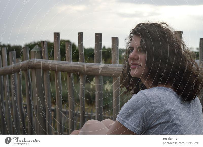 junge hübsche brünette Frau mit lockigen Haaren sitzt nachdenklich vor einem Bretterzaun in den Dünen in Strandnähe und schaut in die Ferne lockige Haare Locken