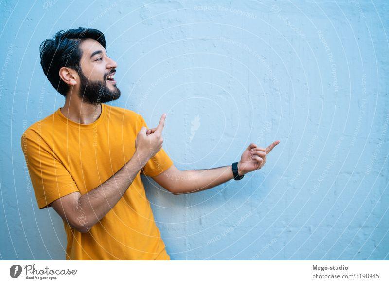 Porträt eines jungen Mannes, der etwas zeigt. Glück schön Mensch Erwachsene Hand Lächeln stehen selbstbewußt Werbung Raum Kopie Hintergrund Menschen vereinzelt