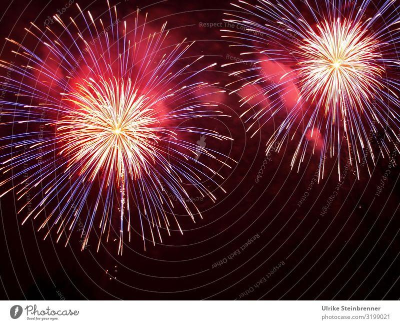 Feuerwerk explodiert in zwei Kreisen mit gelben Funken vor roten Rauch Himmel Licht Nacht Strahlen Explosion leuchten Pyrotechnik Lichteffekte Farben Knall Fest