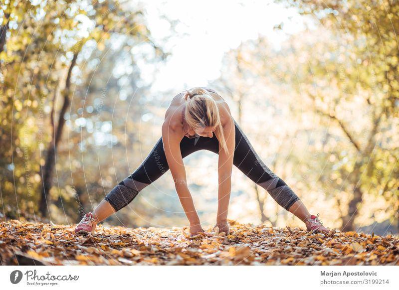 Junge Frau, die sich nach dem Training im Park ausdehnt. Gesundheit sportlich Fitness Wellness Leben Sport Sport-Training Leichtathletik Sportler Joggen feminin