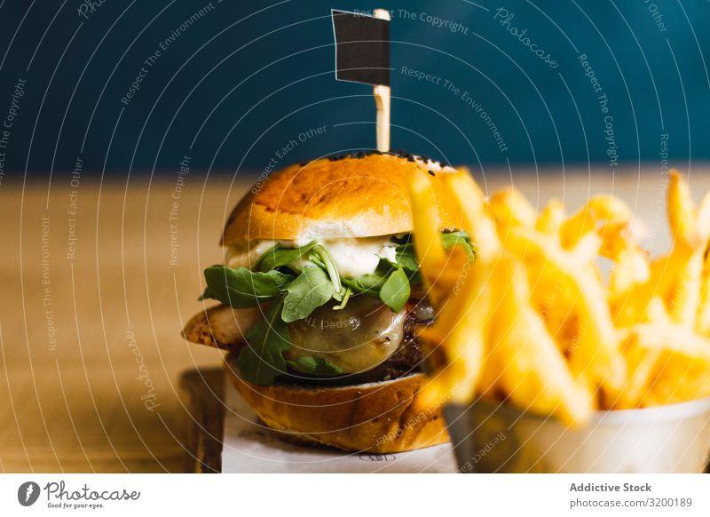Saftig leckerer Burger und Bratkartoffeln auf dem Tisch Dschunke Essen Hamburger geschmackvoll Kartoffeln Lebensmittel Mahlzeit Rindfleisch Brötchen