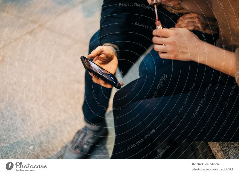 Paare mit Smartphone zusammen auf der Bank benutzend PDA Mitbenutzung sitzen Großstadt Straße Zusammensein interessant Video beobachten Mann Frau Jugendliche