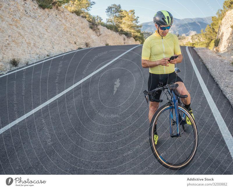 gesunder Mann mit Smartphone nach dem Radfahren auf einer Bergstraße an einem sonnigen Tag Freizeit & Hobby Athlet Sport Ausritt Fahrrad Rennsport
