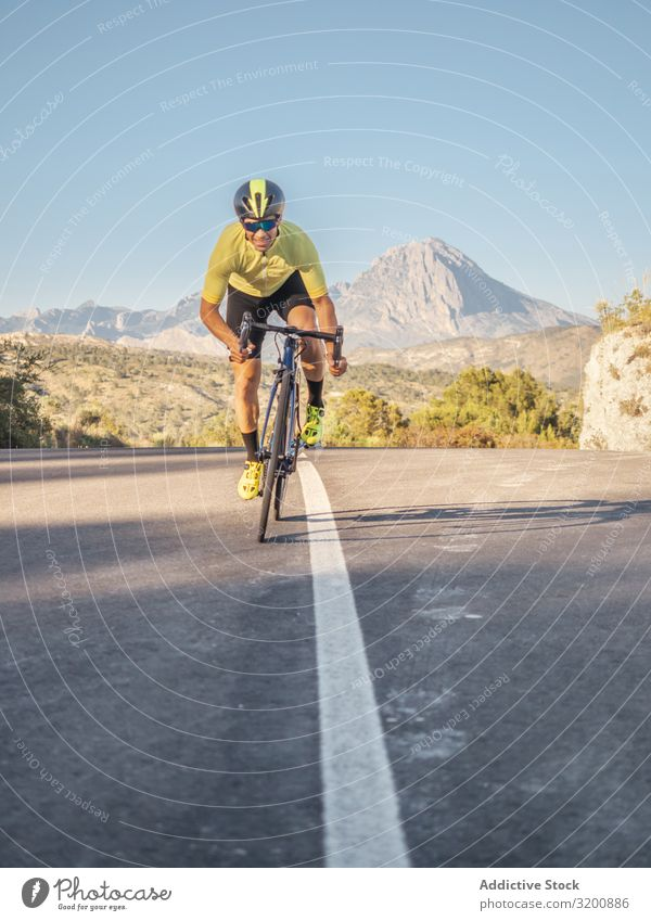 gesunder Mann, der an einem sonnigen Tag auf einer Bergstraße Fahrrad fährt Freizeit & Hobby Athlet Sport Ausritt Rennsport Motorradfahren Außenaufnahme