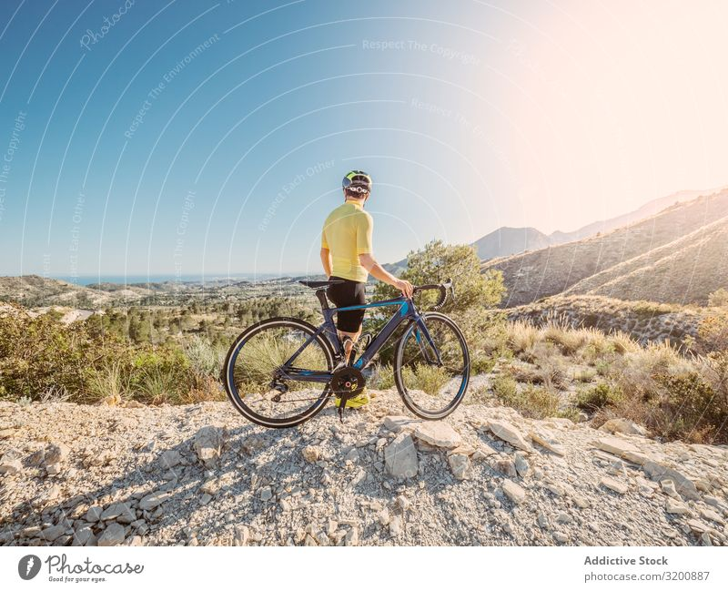 Mann, der sich ausruht und die Aussicht genießt, während er mit dem Fahrrad auf einer Bergstraße fährt Freizeit & Hobby Athlet Sport Ausritt Rennsport