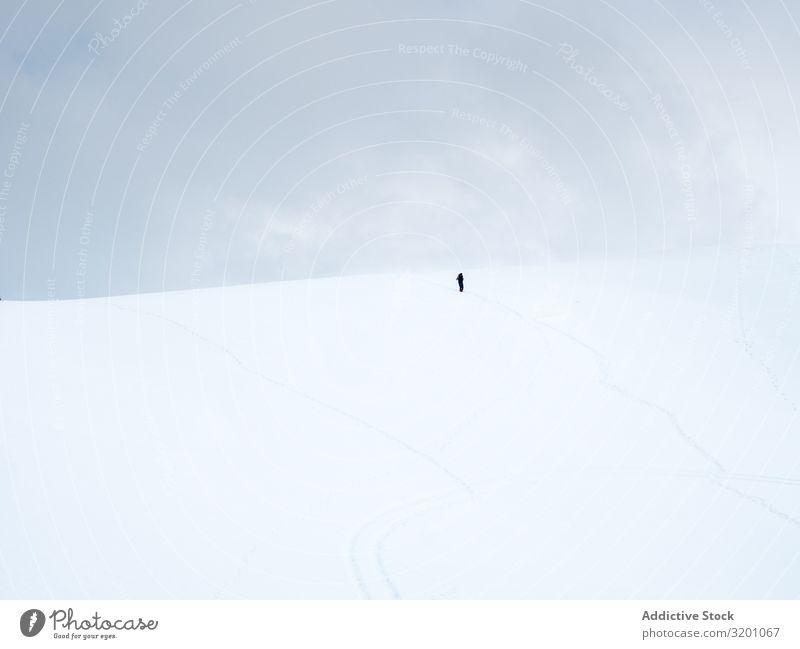 Unbekannter einsamer Reisender beim Spaziergang auf einem verschneiten Hügel Einsamkeit Inspiration Schnee minimalistisch Landschaft Natur Berge u. Gebirge