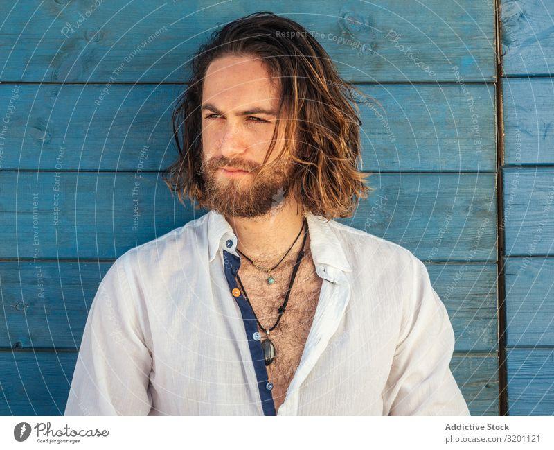 Fröhlicher Kerl sitzt an der blauen Wand Mann Resort ruhig selbstbewußt Lächeln lässig Ferien & Urlaub & Reisen Sommer Lifestyle Freizeit & Hobby ruhen heiter