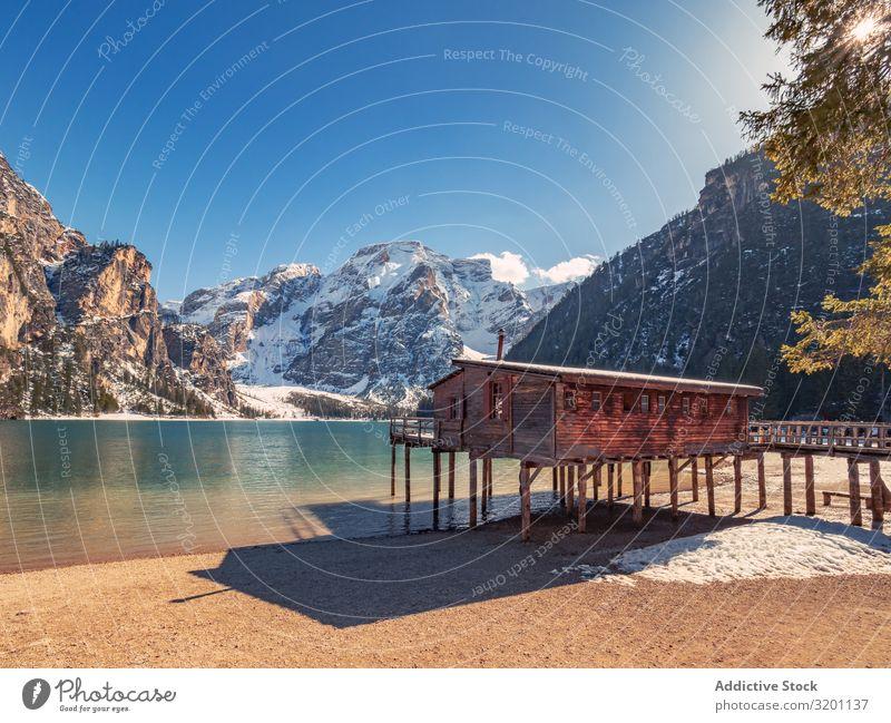 Holzhaus auf Stelzen am stillen See Pfahlhaus Gelassenheit Buhne Natur Meer Felsen Landschaft