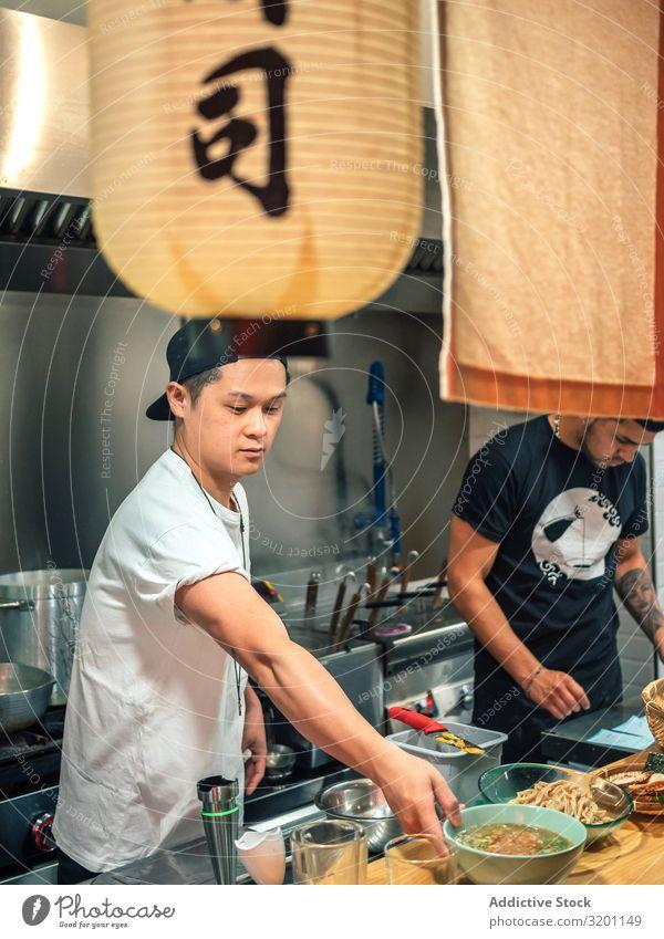 Junge Männer arbeiten in der Küche Mann kochen & garen Ramen Lebensmittel Beruf Japaner Speise Restaurant Arbeit & Erwerbstätigkeit Person gemischter Abstammung