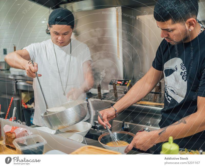 Asiatische Männer, die in der Küche Suppe ausschenken Mann kochen & garen Ramen Topf Lebensmittel Beruf Japaner Speise Restaurant Arbeit & Erwerbstätigkeit