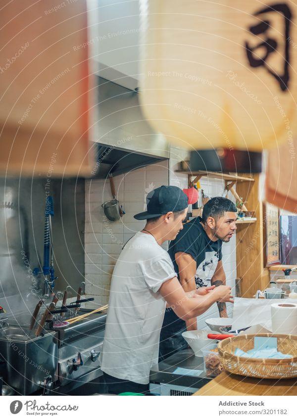 Multiethnische Köche arbeiten in der Küche des Cafes Mann kochen & garen Ramen Lebensmittel Beruf Japaner Speise Restaurant Arbeit & Erwerbstätigkeit