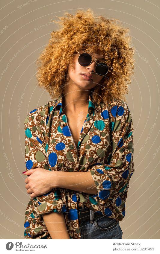 Retro-Frau mit lockigem Haar retro Outfit urwüchsig Sonnenbrille Bluse genießen krause Haare blond Model altehrwürdig Stil trendy Ornament Muster elegant