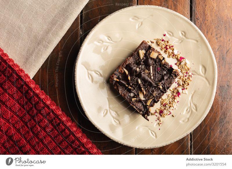 Leckerer brauner Kuchen mit Flocken auf Teller Hafer natürlich Vegane Ernährung vegane Milch Lebensmittel Dessert frisch lecker Holz gebastelt appetitlich