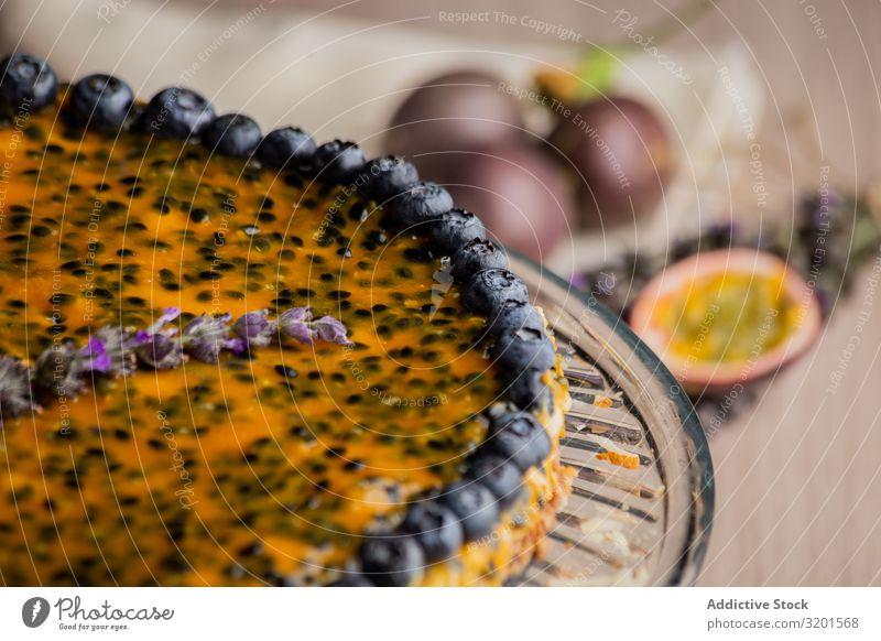 Schmackhafte Passionsfruchttorte mit Heidelbeere dekoriert Pasteten Blaubeeren festlich natürlich Vegane Ernährung Sesam Lebensmittel Dessert frisch lecker Holz