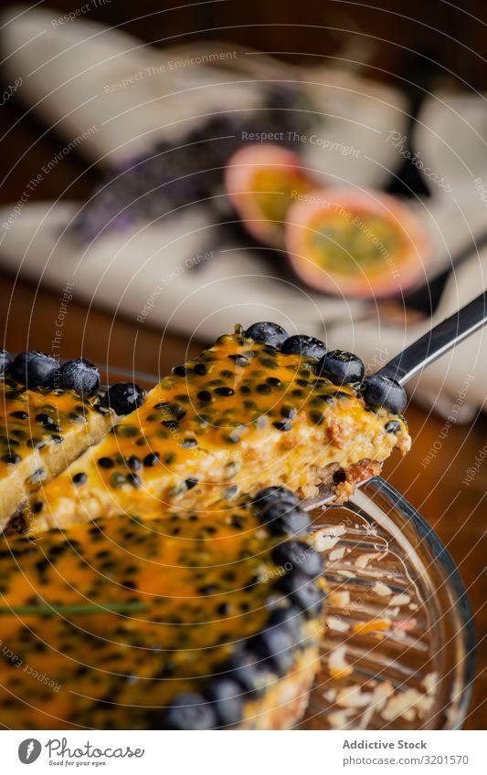 Schmackhaftes Stück Passionsfruchtkuchen mit Heidelbeere dekoriert Pasteten Orange Blaubeeren aufgeschnitten festlich natürlich Vegane Ernährung Lebensmittel
