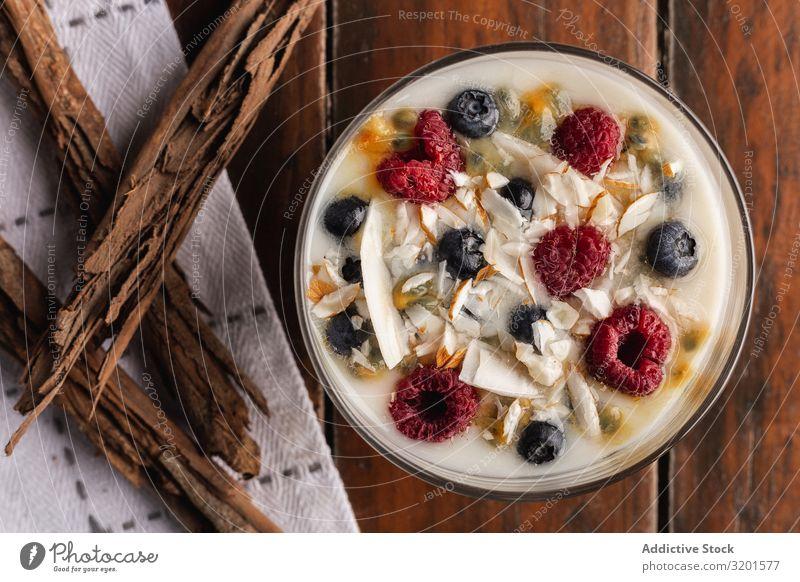 Joghurt in Glasschüssel mit Beeren und Zimtstäbchen Himbeeren Johannisbeeren Flocken Hafer duftig natürlich Vegane Ernährung vegane Milch Lebensmittel Dessert