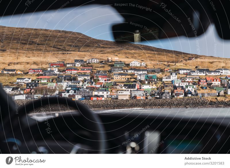 aus dem Auto Blick auf ein kleines buntes Dorf auf den Färöern Stadt Hügel Landschaft Haus Føroyar Außenseite Wetter Himmel Wohnsiedlung Hütten Felsen