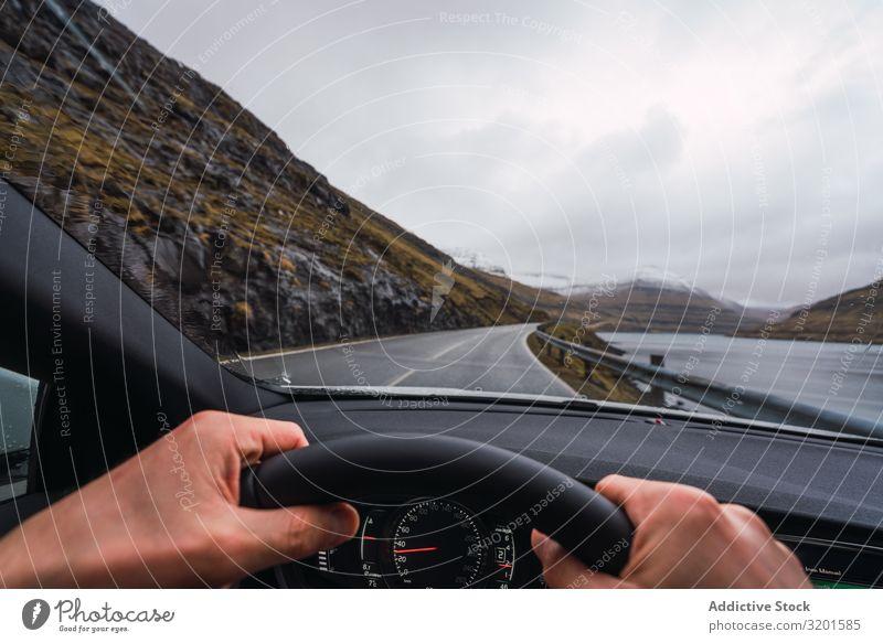 von der Innenseite eines Autos aus die Ansicht einer anonymen Person, die an einem Regentag ein Auto fährt PKW Straße Ausflug Hügel Landschaft Ausritt Wolken