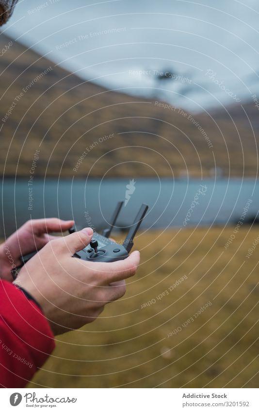 nicht erkennbare Person, die eine Drohne in der Nähe des Sees auf den Färöern kontrolliert abgelegen Technik & Technologie Kontrolle Dröhnen Innovation Radio
