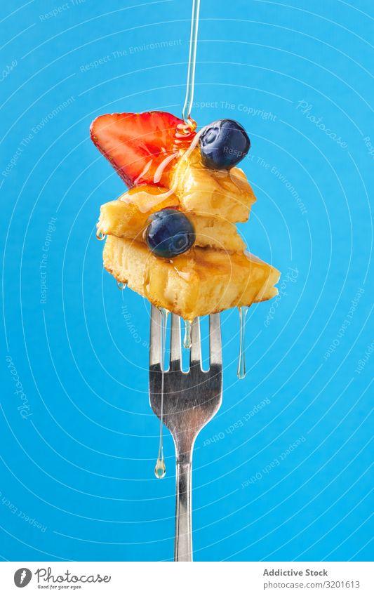 Appetitanregendes Obstdessert mit Honig auf der Gabel Dessert appetitlich Frucht Zusammensetzung süß Erdbeeren Blaubeeren aromatisiert blau Lebensmittel lecker