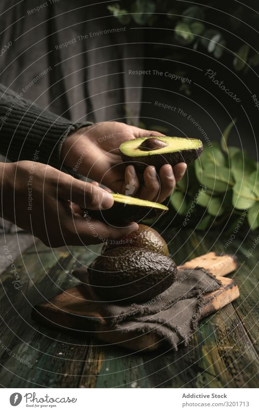 Person, die Avocados an den Händen hält geschnitten Diät exotisch Lebensmittel frisch Frucht grün Hälfte Gesundheit natürlich Natur Ernährung organisch roh reif