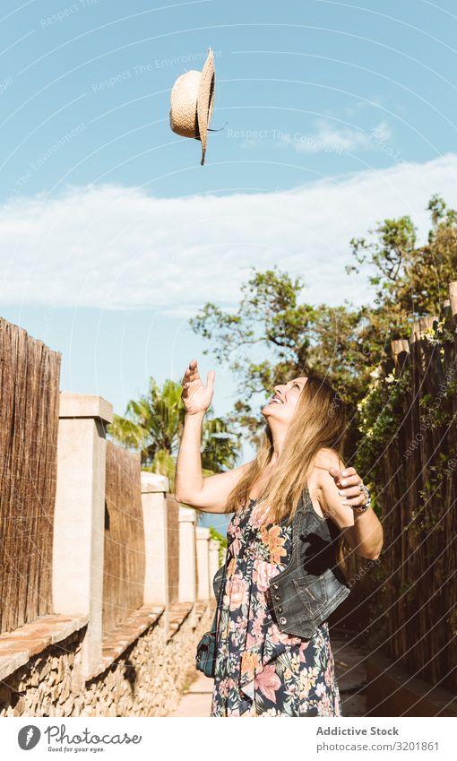 Glückliche Frau, die den Hut hochwirft Strohhut Sommer werfen Ferien & Urlaub & Reisen nach oben heiter Stil Tourismus Gefühle Ausdruck hell Beautyfotografie