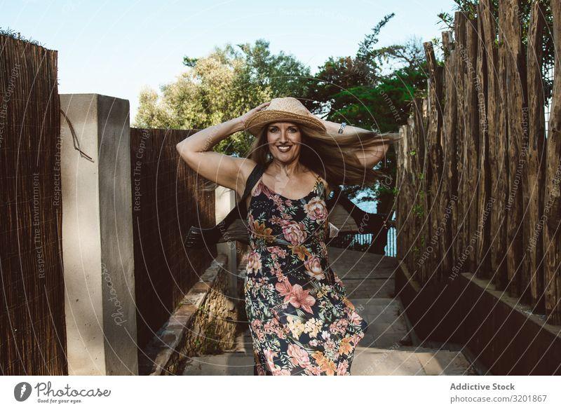 Fröhliche Frau im Sommerkleid dreht sich herum Drehen Kleid Glück Erwachsene Bewegung Ferien & Urlaub & Reisen Strohhut Stil hell Tourismus heiter Gefühle