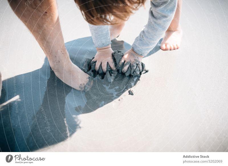 Kind mit Elternteil, das Sand mit Händen und Füßen knetet Kneten klein Strand Barfuß Säuglingsalter niedlich Spielen Freude erkundend schön Elternschaft heiter