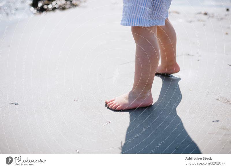 Barfüßiges Kind kurz am Sandstrand klein Strand Barfuß Säuglingsalter niedlich Spielen Freude erkundend schön heiter Kindheit Fundstück hübsch reizvoll