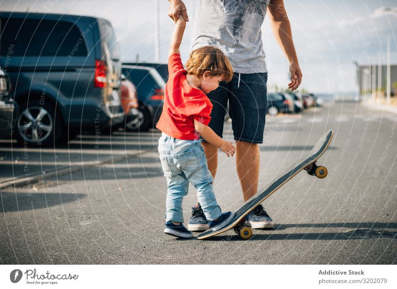 Mann mit Kind trainiert mit dem Skateboard Vater genießend Elternschaft laufen Ferien & Urlaub & Reisen Familie & Verwandtschaft Lehre Zusammensein Freude