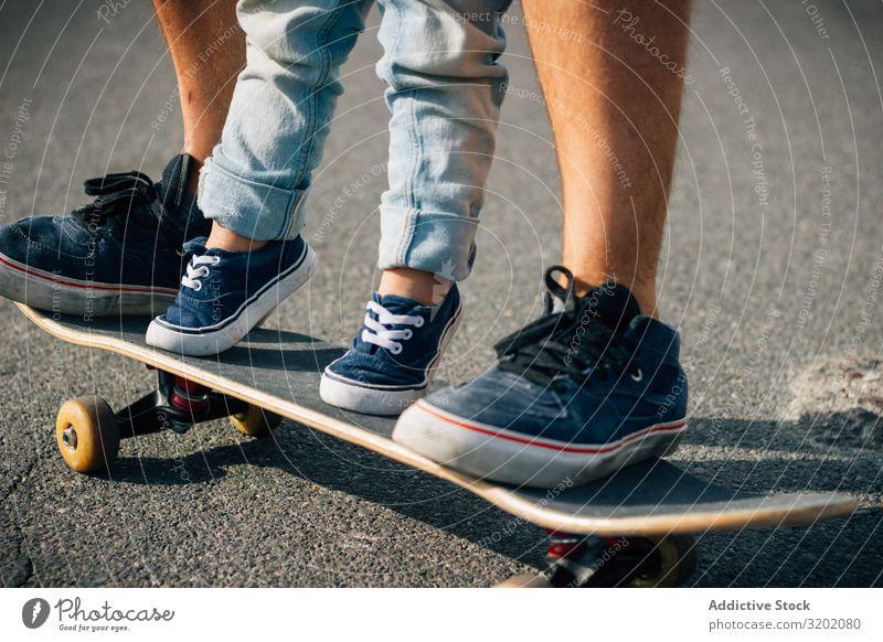 Mann mit Kind trainiert mit Skateboard auf Asphalt Vater genießend Elternschaft laufen Ferien & Urlaub & Reisen Familie & Verwandtschaft Lehre Zusammensein