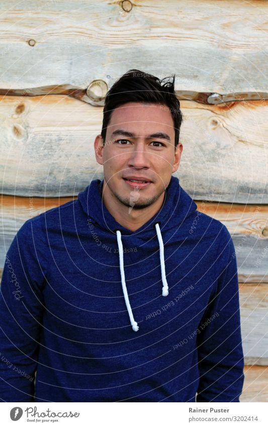 Junger Mann im Hoodie vor Holzwand maskulin Jugendliche Erwachsene 18-30 Jahre 30-45 Jahre Mauer Wand Pullover Kapuzenpullover schwarzhaarig Neugier blau grau