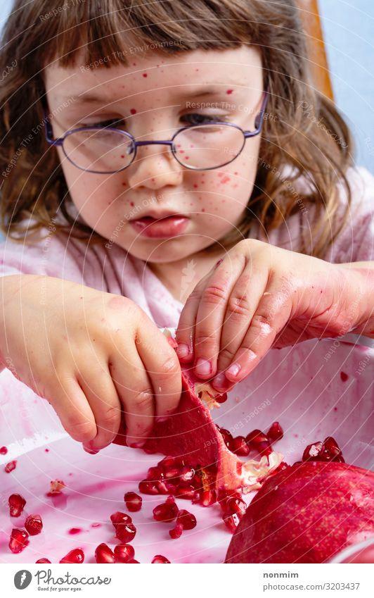Mädchenschale Granatapfel. Gesicht verschmutzt von roten Flecken Frucht Dessert Ernährung Vegetarische Ernährung Kind Brille dreckig frisch natürlich Neugier