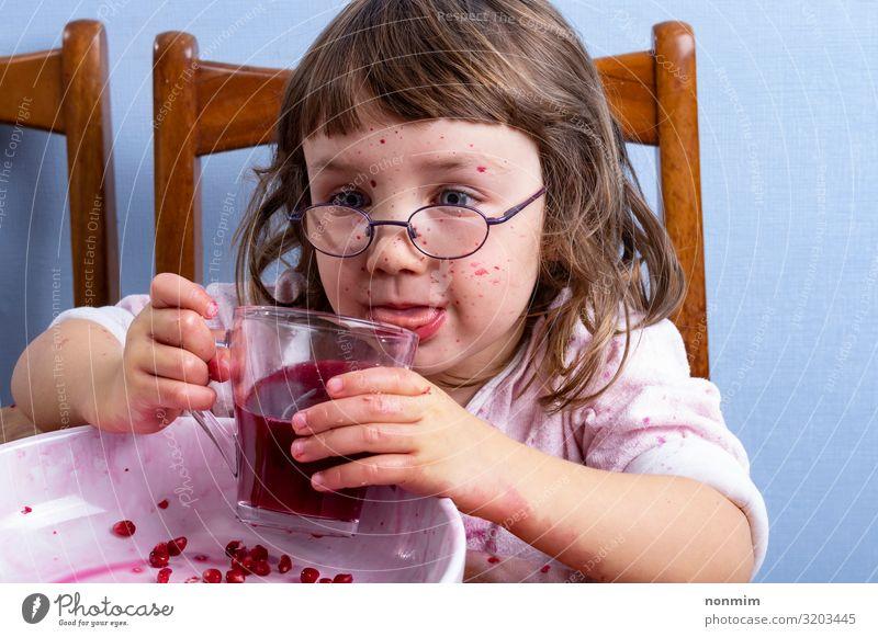 Mädchen schmeckt Granatapfelsaft. Gesicht verschmutzt durch rote Flecken Frucht Dessert Ernährung Vegetarische Ernährung Diät Getränk Saft Lifestyle exotisch