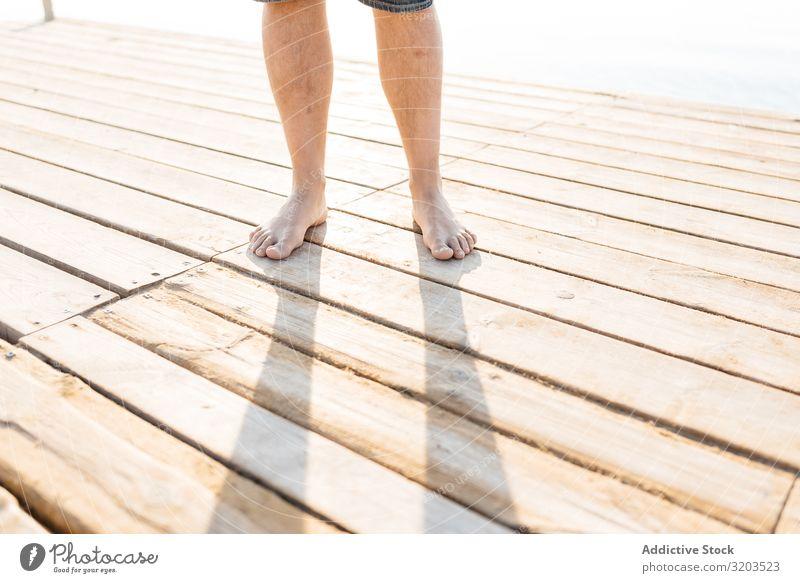 Beine eines Erwachsenen, der auf einem Holzsteg im Sonnenlicht steht Mann stehen Anlegestelle Fuß Beschnittansicht Sommer Zufriedenheit Körperteil Natur