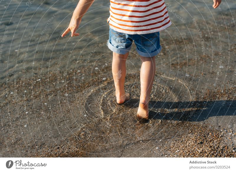 Verspielter kleiner Junge, der ins Wasser tritt seicht platschen Schritt spielerisch Sommer Ferien & Urlaub & Reisen Kind Freizeit & Hobby Spielen Meer Strand